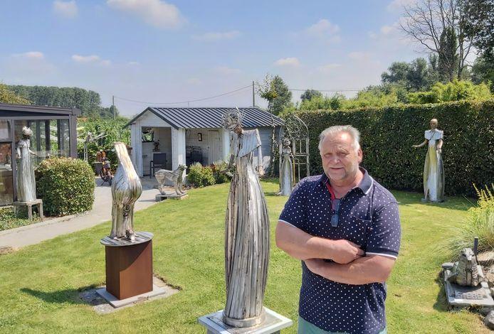 Roger Pintens Jr. bij de beelden in zijn tuin.