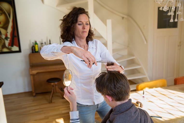Een moeder knipt thuis haar zoon omdat de kappers gesloten zijn.  Beeld Arie Kievit