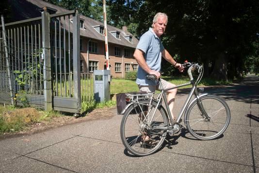 Dick Veerman nodigt belangstellenden uit om de Fliegerhorst Deelen met de fiets te verkennen bij de ingang van Kamp Koningsweg Noord. Links van hem een van de kazernebunkers van de Blitzmädel, de 450 medewerkersters van de Luftwaffe.