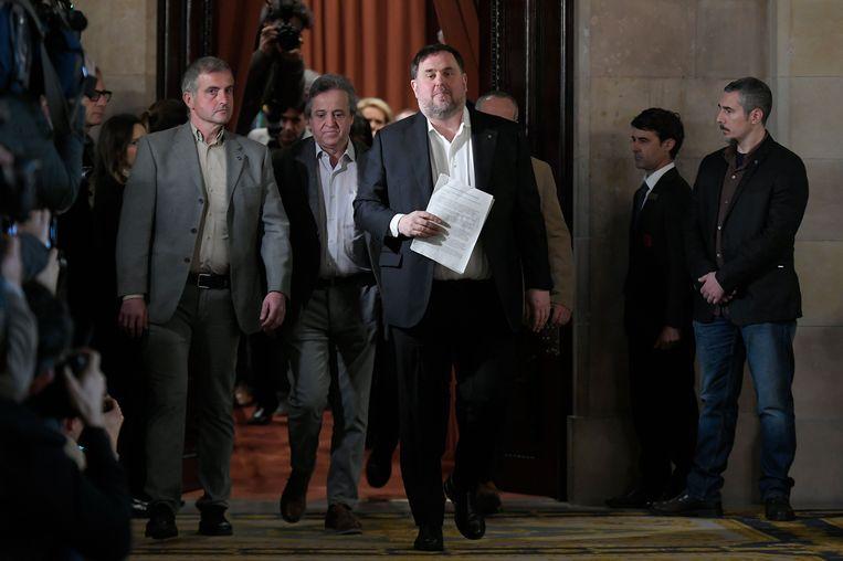 Oriol Junqueras (met papieren) verlaat eind januari een hoorzitting van een regionaal parlementair comité in Barcelona. Onder politie-escorte is hij met andere veroordeelde Catalaanse politici vanuit de gevangenis naar de bijeenkomst gebracht. Beeld AFP