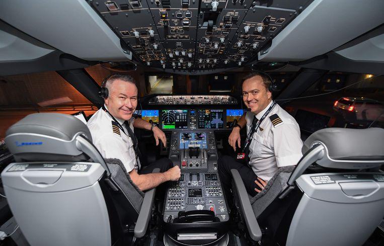 Piloten Sean Golding (L) en Jeremy Sutherland in de cockpit van de Qantas Boeing 787 Dreamliner voor aanvang van de vlucht. Beeld AFP