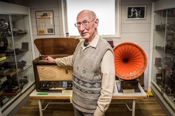 Henk de Groot met twee pronkstukken uit zijn radiomuseum. Links een Tefifon (een draadrecorder) uit het midden van de jaren 50, rechts een Jumbo tafelgrammofoon uit 1915.
