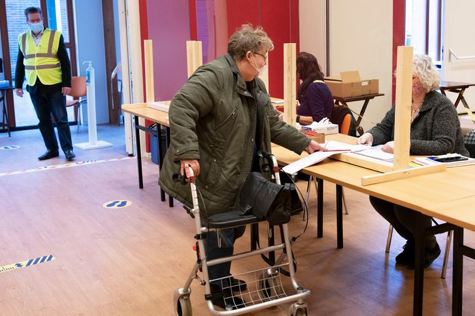Jopie Pluijser neemt maandagochtend haar stemformulier in ontvangst in het stembureau in de Allemanswaard in Amerongen. Op de achtergrond Gert-Jan van den Brink.