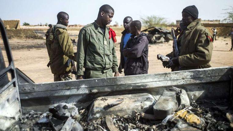 Malinese soldaten bij een uitgebrande auto in Konna Beeld afp
