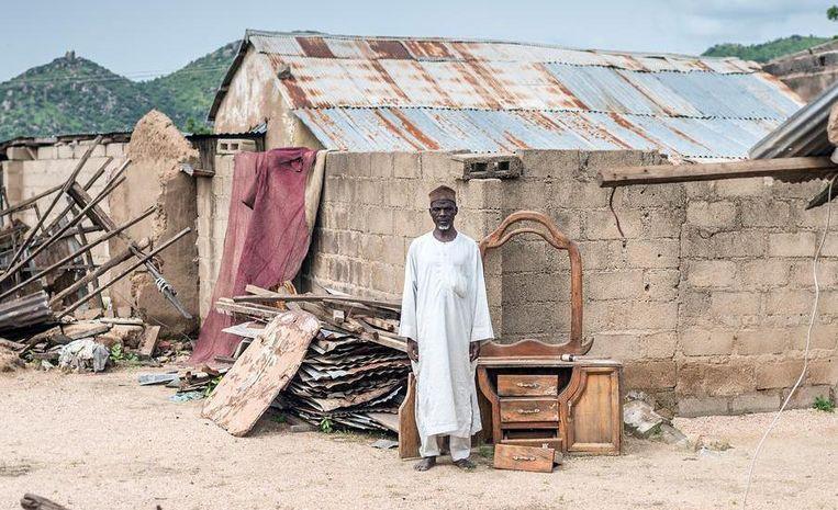 Een man staat te midden van de resten van zijn huis in Noord-Nigeria Beeld Sven Torfinn