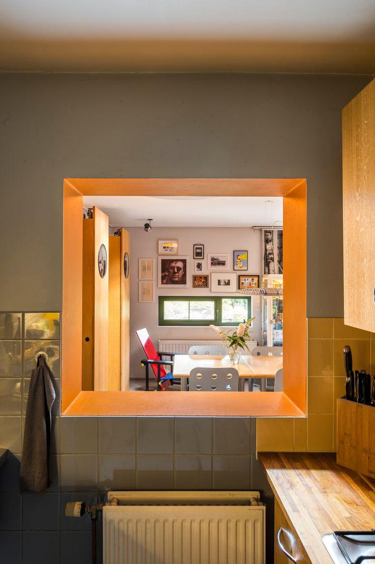 Een nis in de muur voorziet de keuken van natuurlijk licht en zorgt voor een connectie met de eetkamer.In de nieuwe achterbouw koos Huub bewust voor een smal raam op ooghoogte dat uitkijkt op de tuin. Beeld Luc Roymans