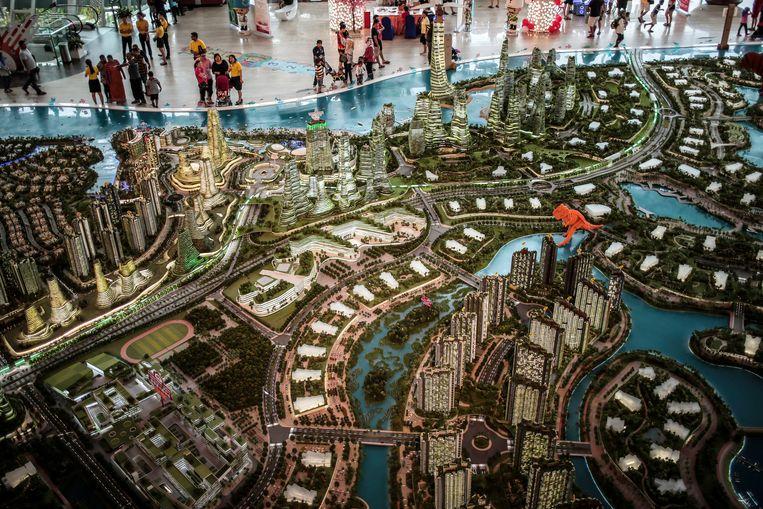 Belangstellenden bekijken een maquette van het project Forest City in de Maleisische stad Johor Bahru. Beeld EPA