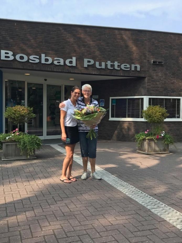 De 200.000ste bezoeker van 2018 in het Bosbad Putten, mevrouw Van Doornik, krijgt een bos  bloemene van de receptioniste Monique.