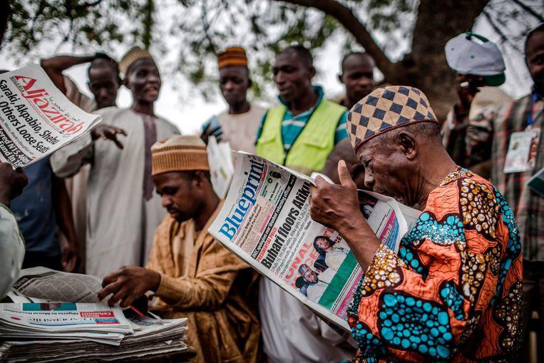 Een man leest een krant waarin de overwinning van de zittende president Muhammadu Buhari wordt aangekondigd, na de uitslag van de presidentsverkiezingen in Nigeria op 27 februari 2019. Beeld AFP