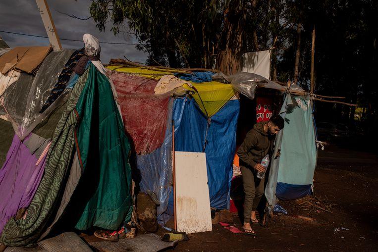 Een migrant verlaat zijn 'tent', bestaande uit doeken, vuilniszakken en slaapzakken. Onder het mom van coronarestricties staat de Spaanse regering maar weinig vluchtelingen toe door te reizen . Beeld Getty Images