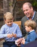 De Britse prins Louis (r) kijkt nieuwsgierig toe terwijl zijn broer prins George (m) de fossiele haaientand aan een nauwkeurig onderzoek onderwerpt. Vader prins William (R) moet hartelijk lachen om het cadeautje van Sir David Attenborough.
