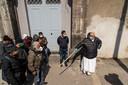 Een geestelijke houdt orde voor de deur van een kerkelijk centrum waar eten wordt uitgedeeld aan een lange rij mensen