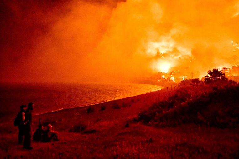 Het gebied rondom de Griekse kustplaats Loutraki trekt normaal gesproken toeristen die er komen voor thermale baden, strand en cultuur. Maar een grote natuurbrand zorgde gisteren voor een uittocht uit de badplaats. Inwoners werden geëvacueerd, de brandweer is met groot materieel uitgetrokken. Rookwolken waren tot in Athene te zien.  Beeld EPA