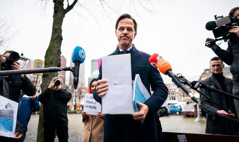 Gedupeerde ouders van de toeslagenaffaire overhandigen in Den Haag een 'lege donatiedoos' aan premier Mark Rutte. Beeld Freek van den Bergh / de Volkskrant