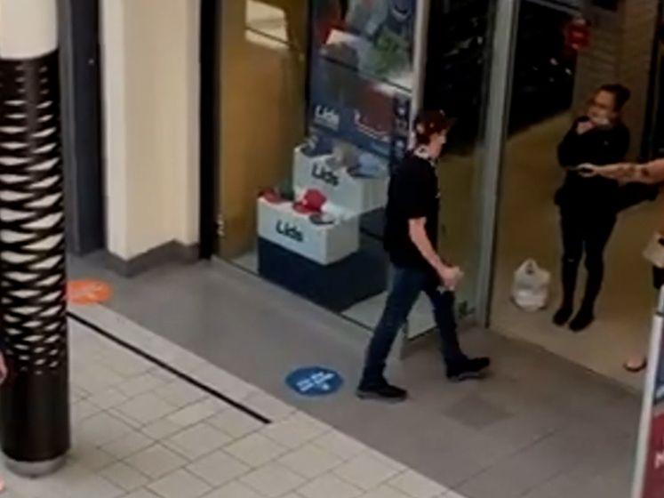 Man wandelt casual langs vrouw die gezin bedreigt met een wapen