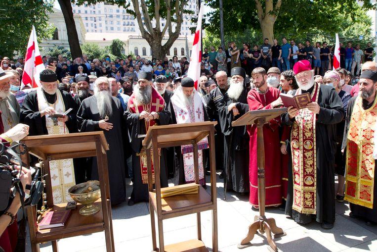 Georgisch-orthodoxe priesters gaan voor in gebed tijdens het blokkeren van een pride-optocht in de hoofdstad Tblisi op 5 juli.  Beeld AP