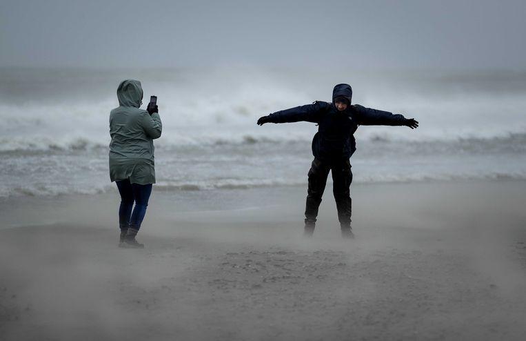 Wandelaars vandaag op het strand tijdens storm Ciara.  Beeld ANP