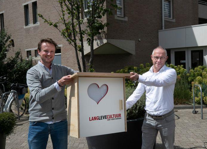 Bibliotheek-directeur Robin Verleisdonk  overhandigt een minibieb aan locatiemanager Jos Mies van de Pannehoeve.