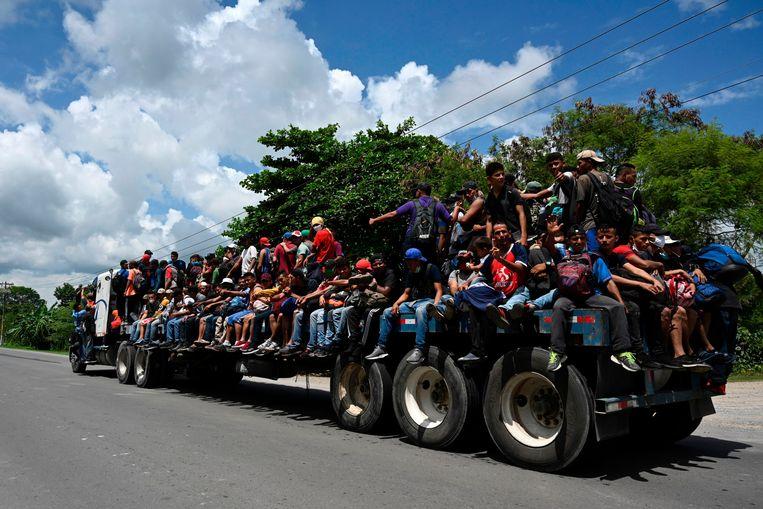Een deel van de migrantenkaravaan zit op een grote truck. Beeld AFP