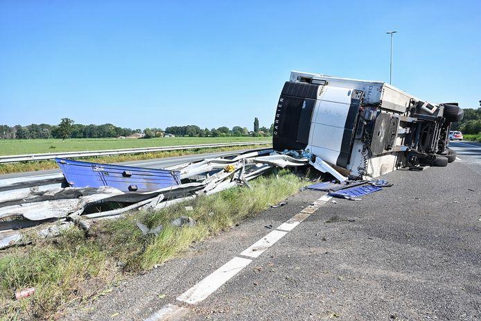 De gekantelde vrachtwagen raakt de vangrail die de snelweg van elkaar scheidt