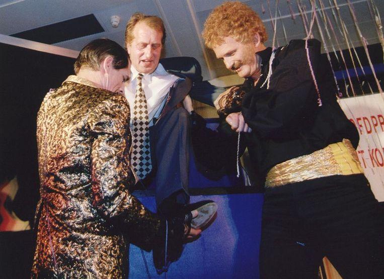 In het Letterkundig Museum in Den Haag trekt het duo Jacobse en Van Es (Kees van Kooten en Wim de Bie) Gerrit Komrij met vereende krachten uit een grote doos bij de uitreiking in 1993 van de door Komrij gewonnen P.C. Hooftprijs. Beeld ANP