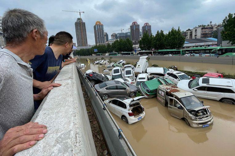 Inwoners van Zhengzou overschouwen de ravage die de storm heeft achtergelaten.  Beeld AFP
