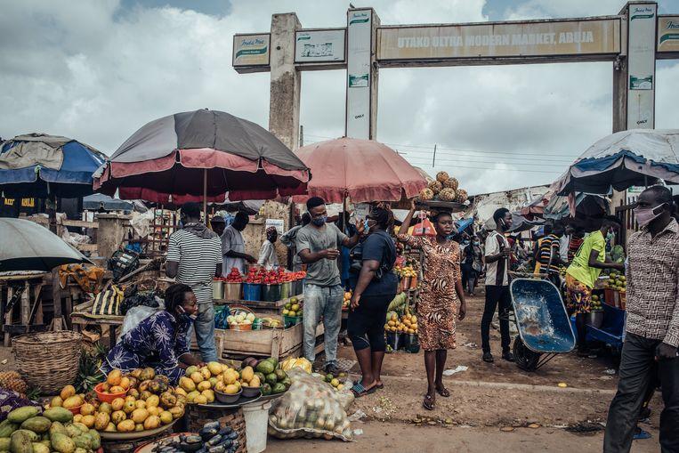 Verkopers brengen waren aan de man op een markt in Abuja, Nigeria.'97 procent van de Nigeriaanse export bestaat uit olie. De gevolgen voor dat land zijn enorm', zegt Collier.  Beeld Bloomberg via Getty Images