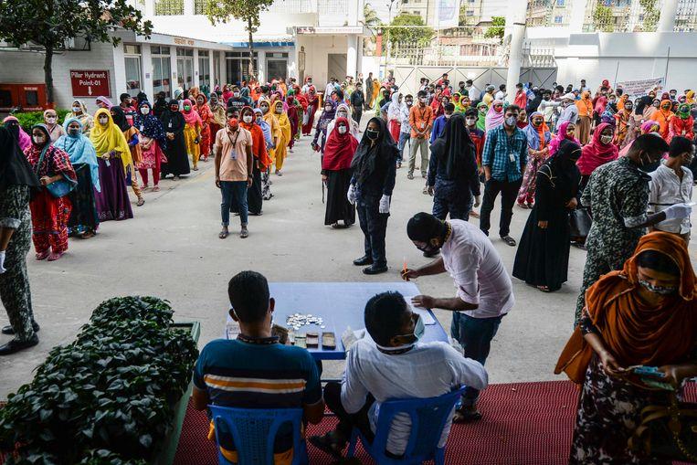 Medewerkers van een kledingfabriek in Bangladesh staan in de rij voor hun salaris.  Beeld AFP