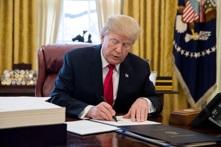 Donald Trump ondertekent een wet in het Oval office. Beeld EPA