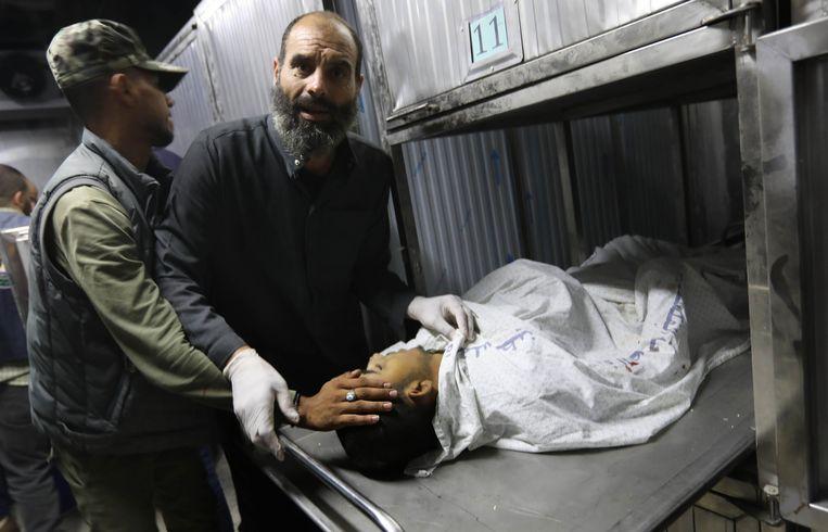 Een Palestijnse man bij een lichaam in het mortuarium in Gaza Stad. Bij de gevechten van de afgelopen twee dagen zijn 34 Palestijnen om het leven gekomen.  Beeld AFP