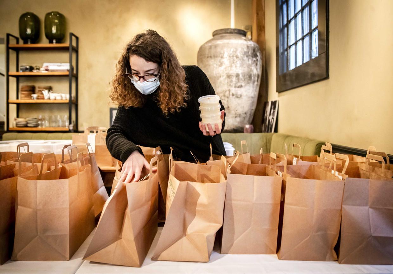Een medewerker maakt afhaalmenu's klaar in restaurant Breda.  Beeld ANP