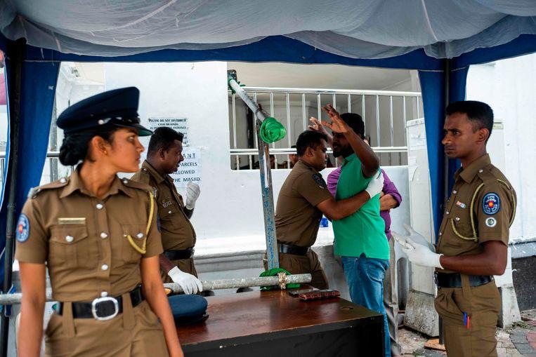 Een politieman fouilleert een moslim bij aankomst bij een moskee in Colombo, Sri Lanka. Beeld AFP