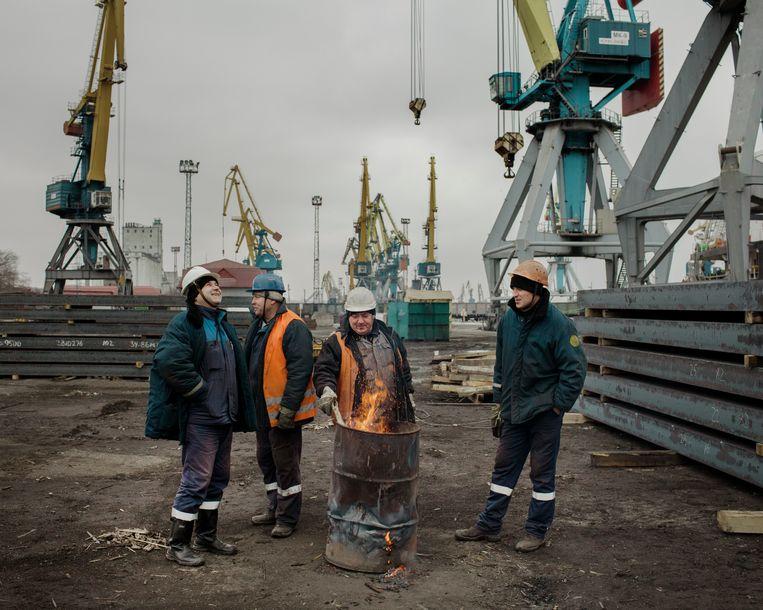 Havenwerkers in Marioepol warmen zich aan een vuurtje in een vat. Beeld Emile Ducke