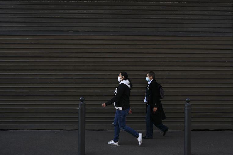 Wandelen in een winkelstraat in de Franse stad Marseille in coronatijd. Zaterdag mogen in heel Frankrijk 'niet-essentiële winkels weer open.  Beeld AFP