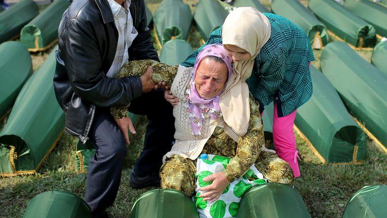 Vrouwen huilen bij de doodskisten van hun familieleden in Srebrenica, Bosnië. Beeld EPA