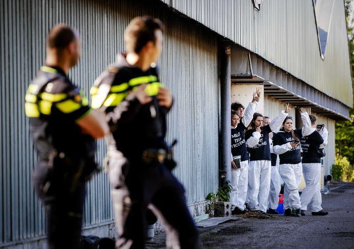 De actievoerders staan binnen, terwijl de politie toekijkt.