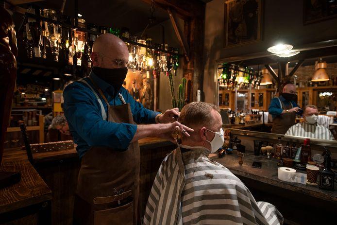 """Bram Verschoor in de stoel van de Rijssense Kapper Joop.  """"Zolang je m'n oren maar laat zitten"""", zegt de eerste klant over de gewenste coupe."""