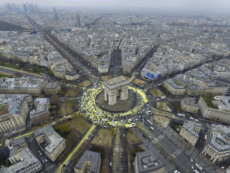 Gele verf rond de Arc de Triomphe. De verf symboliseert de zon en haar stralen. Beeld REUTERS