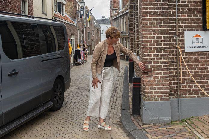 Mariejanne Schoppert aan het begin van de Brouwerstraat waar ze schade aanwijst aan het pand van het Prins Mauritshuis.