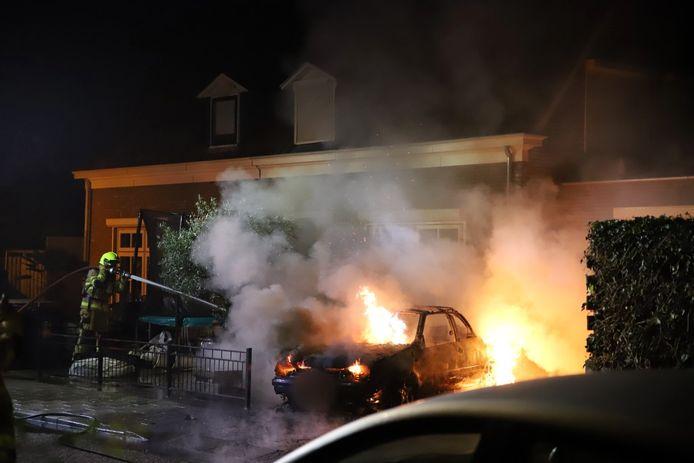 De brandweer blust de brandende auto aan de Raamweg in Tricht.