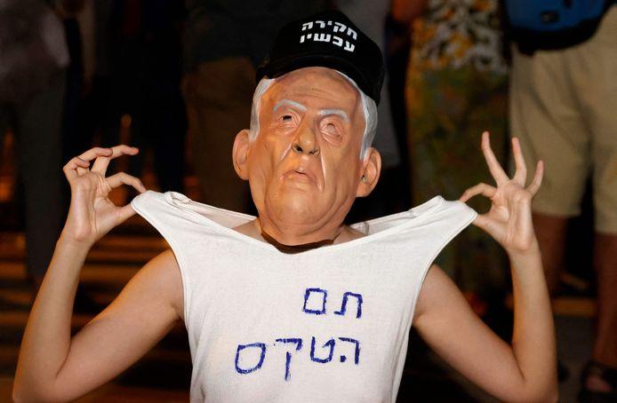 """Israëlische betoger met een masker van premier Benjamin Netanyahu en de tekst """"het feest is over"""" op het T-shirt"""