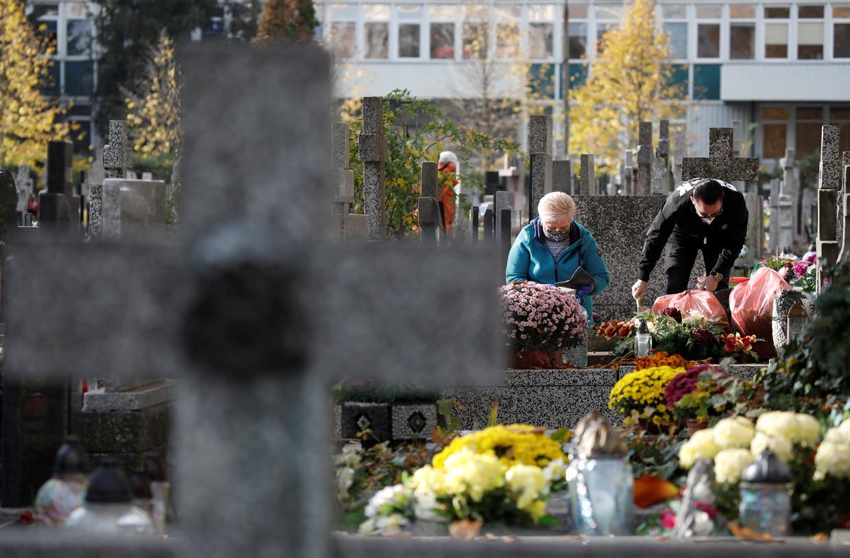 Mensen bezoeken een graf op de dag voor Allerheiligen in Warschau.