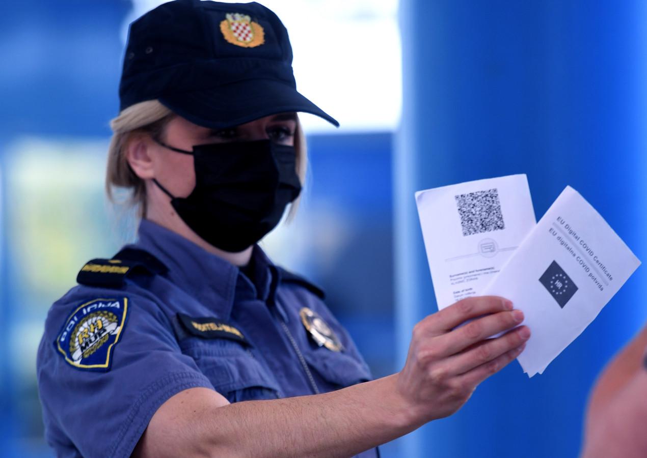 Een agent met een coronapaspoort.