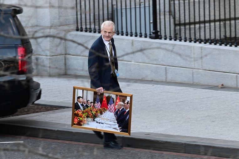 Witte Huis-adviseur Peter Navarro verlaat het Witte Huis met een foto van Donald Trump aan een diner met de Chinese president Xi Jinping.  Beeld Reuters