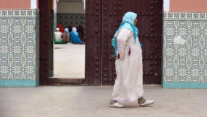 Een vrouw in Marokko in een traditioneel lang gewaad.