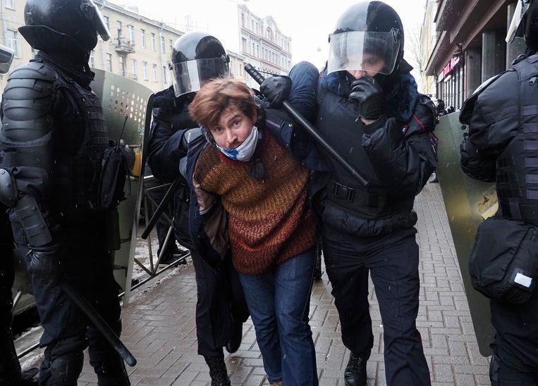 Een demonstrant in Sint Petersburg wordt gearresteerd. In totaal werden zondag zo'n vijfduizend aanhoudingen verricht. Beeld AP