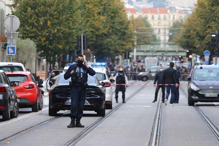 Agenten zetten een straat in Nice af, nadat een man bij een kerk mensen heeft neergestoken.  Beeld AFP