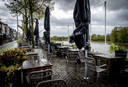 Een leeg terras op een druilerige dag in het centrum van Arnhem. De terrassen zijn weer geopend, maar het weer zorgt ervoor dat gasten wegblijven.