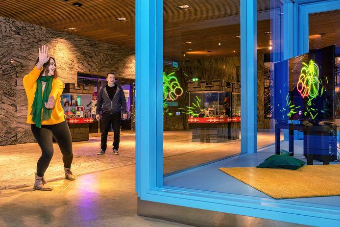 In station Breda is een nieuwe interactieve game geplaatst. Alina Anikina van Sassybot demonstreert het spel terwijl haar collega Tino van der Kraan toekijkt.