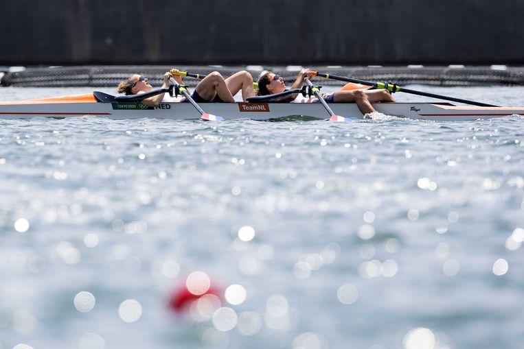 Marieke Keijser en Ilse Paulis liggen ontgoocheld in hun boot. Ze hadden zicht op goud, maar moesten genoegen nemen met brons. Beeld ANP